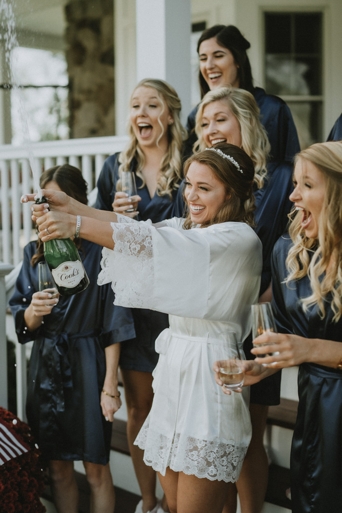 Bride opens bottle of champagne with bridesmaids before hudson valley wedding