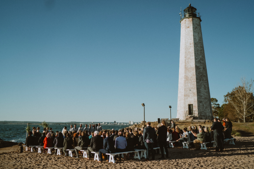 Guests at beach wedding ceremony in long island by lighthouse