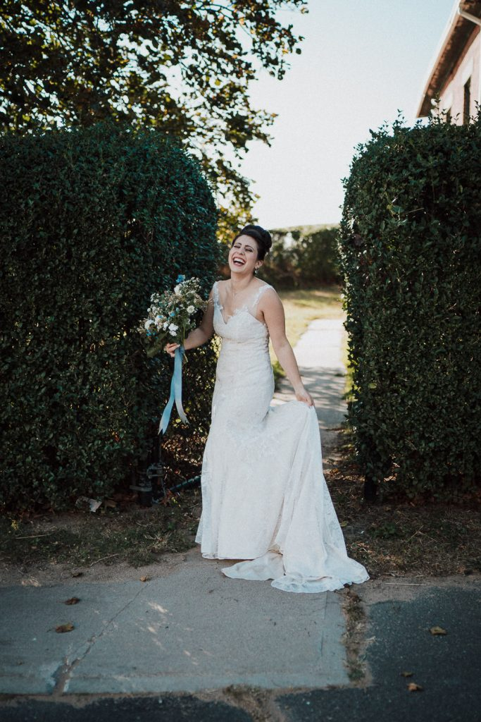 Bride holding wedding dress and laughing at hudson valley wedding