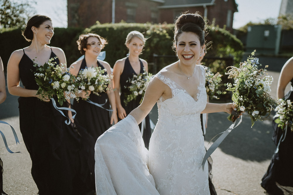 Bride and bridesmaids laugh on parking lot at hudson valley wedding
