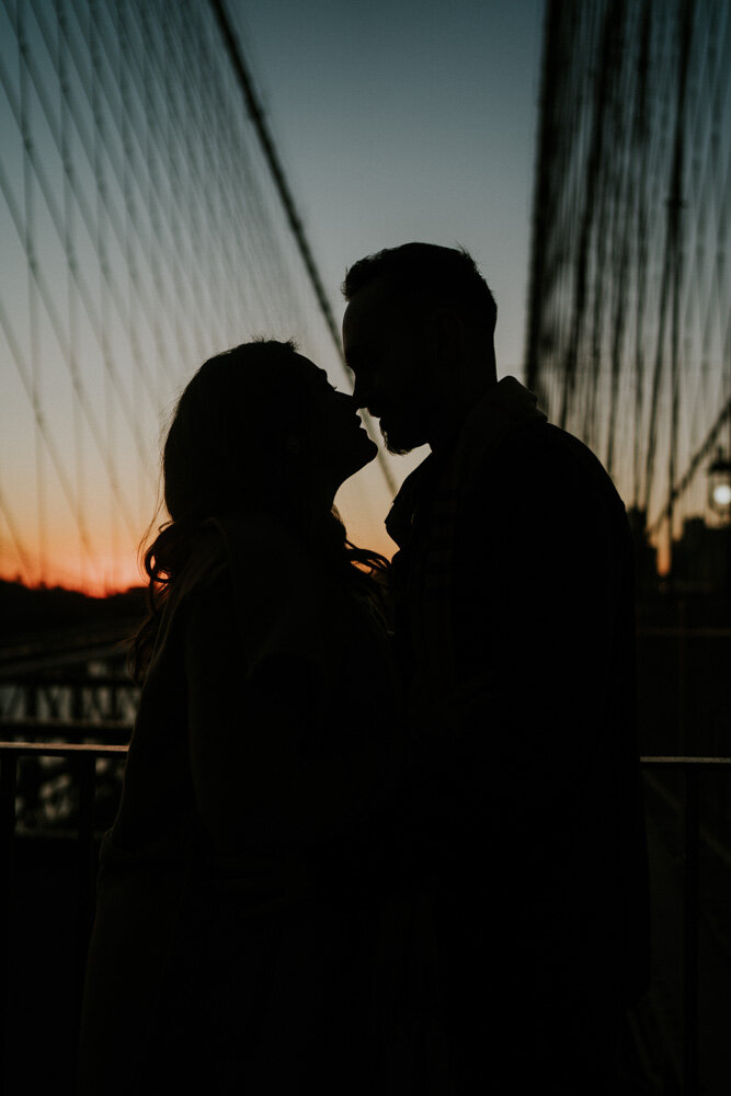 Silhouette of couple at sunrise on brooklyn bridge during engagement session