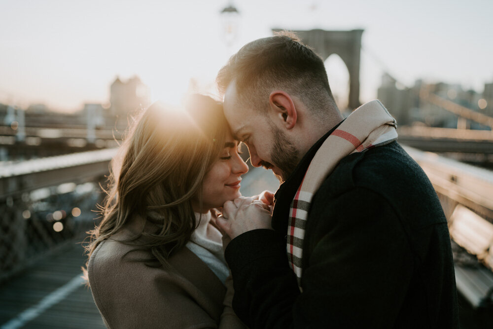 Couple snuggling on brooklyn bridge at sunrise during engagement session