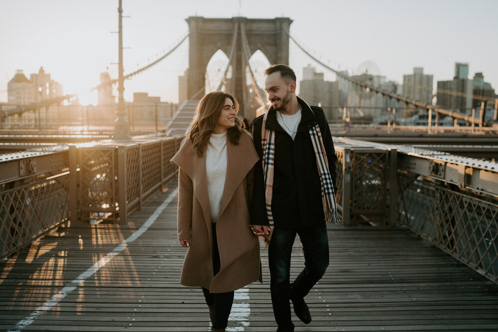 Couple walking on brooklyn bridge at sunrise during engagement session