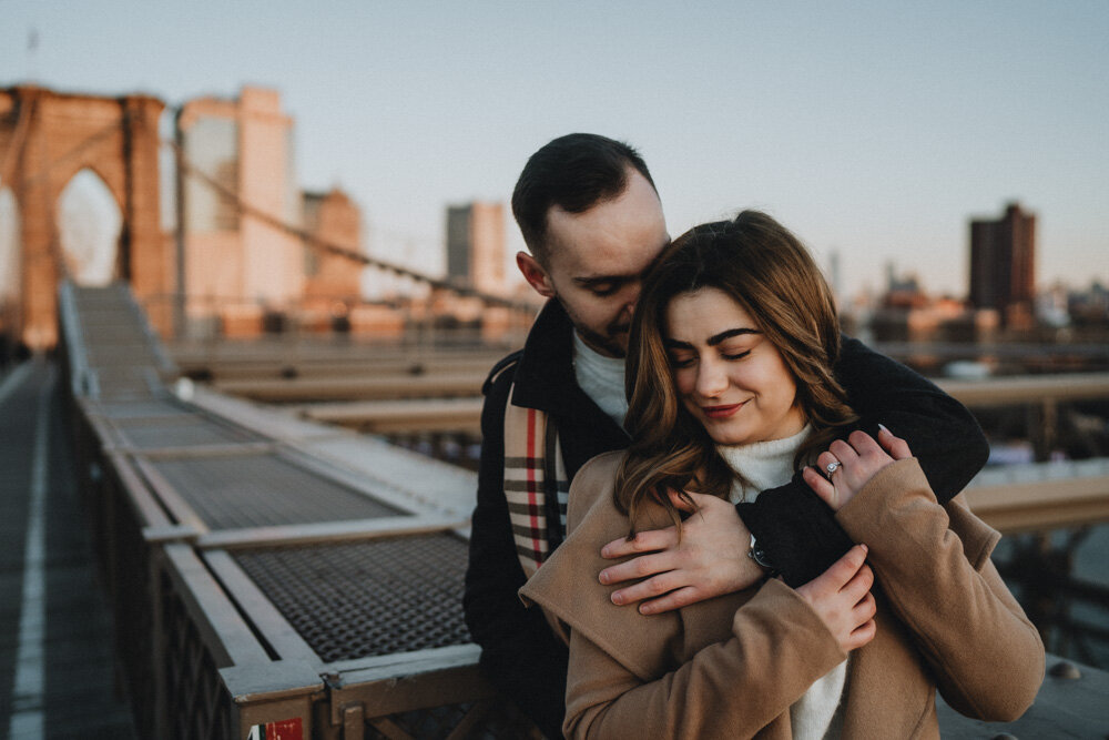 Couple snuggling on brooklyn bridge during engagement session