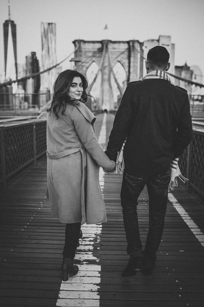 Woman holds boyfriend's hand on brooklyn bridge and glances back at photographer