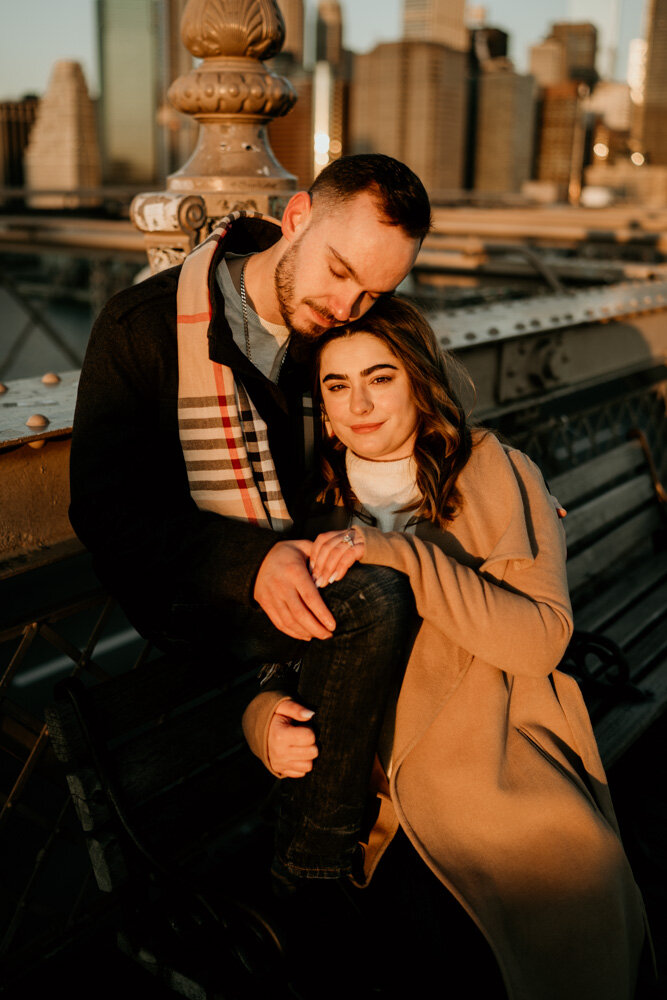 Couple snuggling on park bench at sunrise and looking at photographer