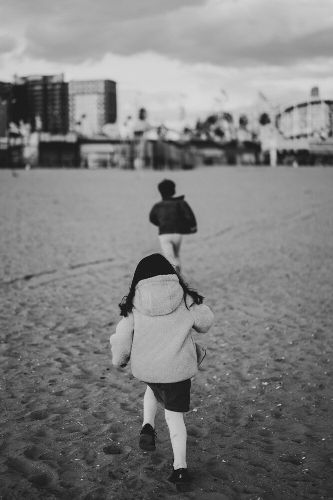 Brother and sister run during family session at coney island beach