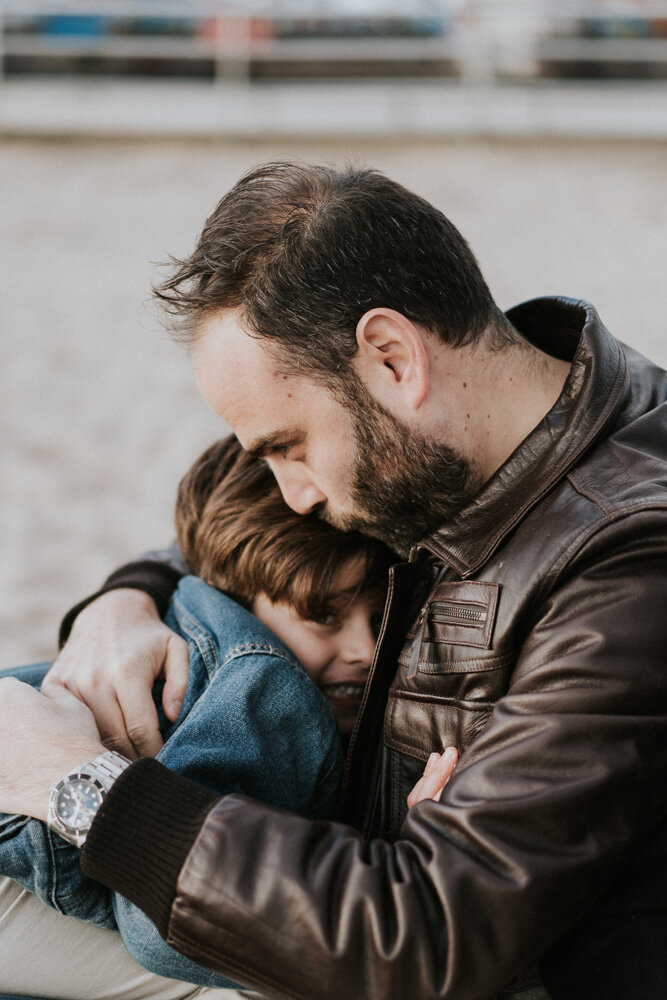 Dad and son snuggle during family session at coney island beach
