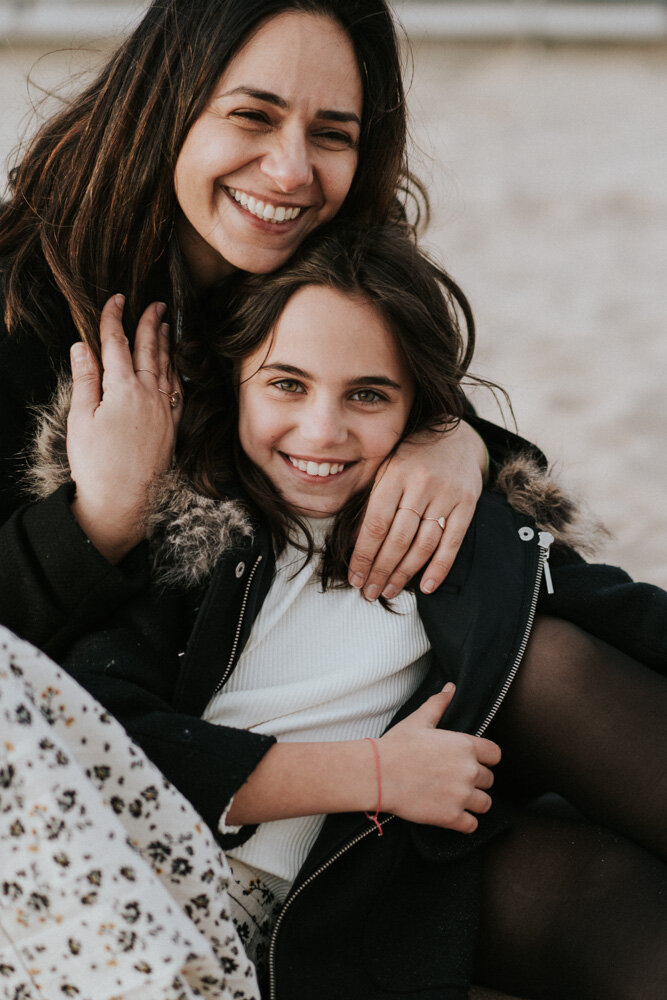 Mom and daughter laugh during family session at coney island beach