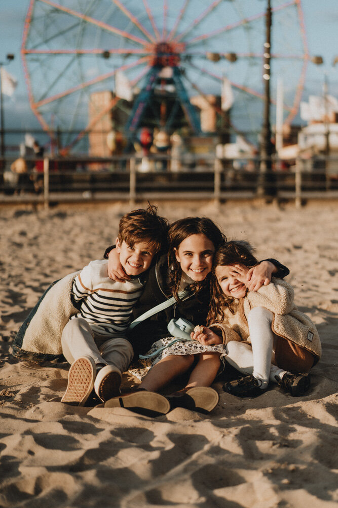 Three kids smile at photographer during family session at coney island beach