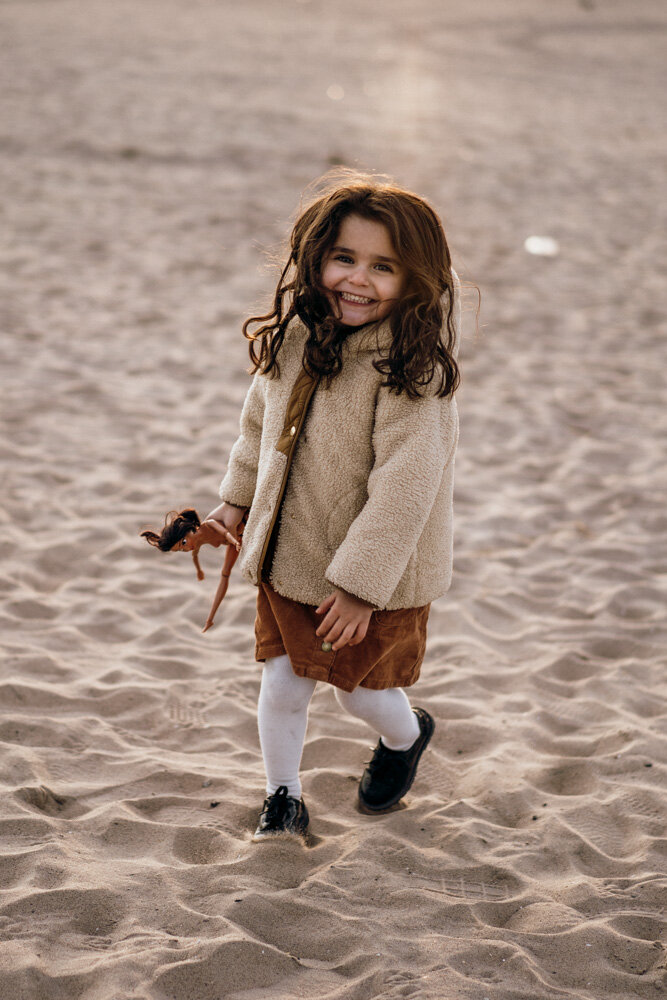 Young girl smiles at photographer during family session at coney island beach