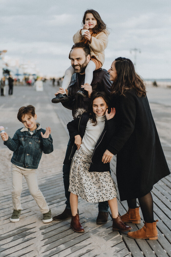 Parents and three kids goofing around during family session at coney island
