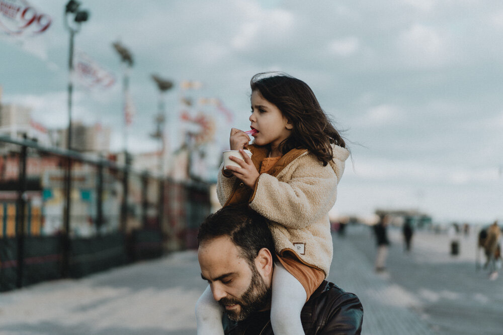 Young girl eats ice cream on dad's shoulders during family session at coney island