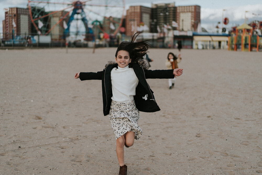 Young girl runs during family session at coney island beach