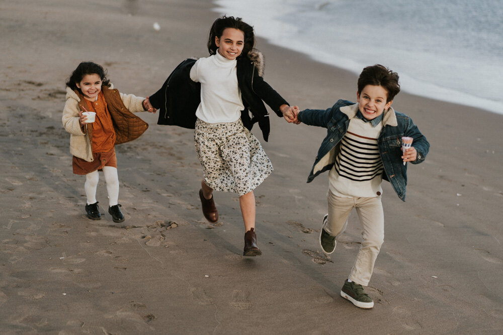 Three kids hold hands during family session at coney island beach