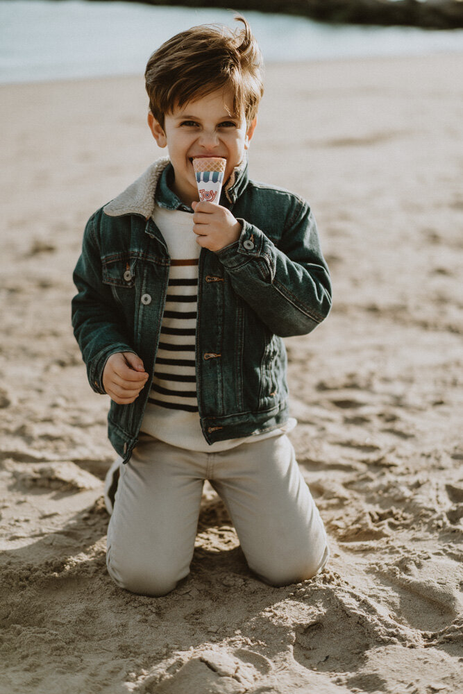 Young boy eats ice cream during family session at coney island beach