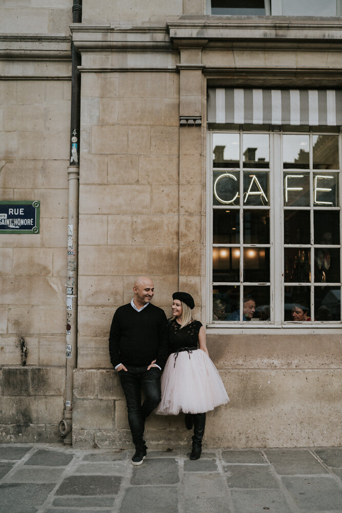 Couple standing by cute cafe during paris engagement session