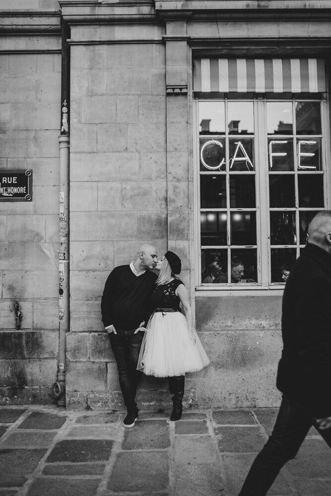Couple kissing by cute cafe during paris engagement session