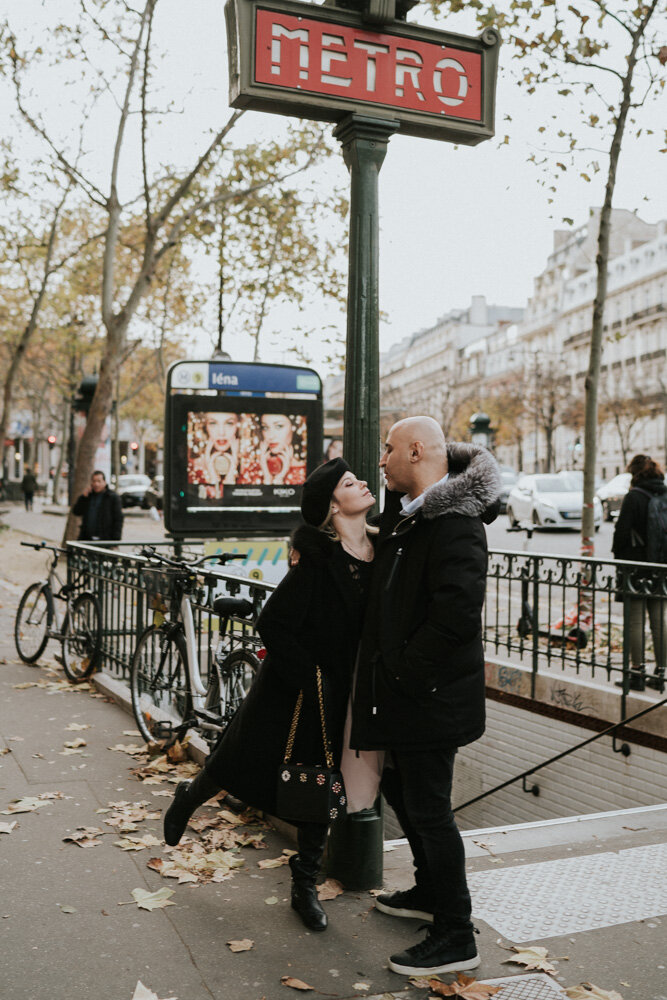 Couple kissing by old metro station during paris engagement session