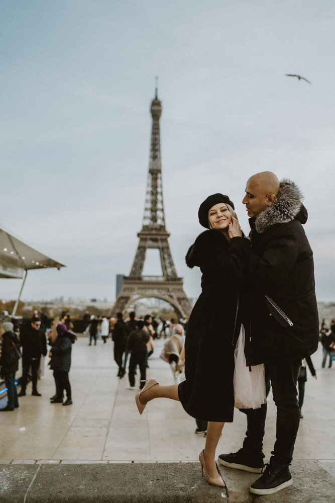 Couple kissing in front of eiffel tower during paris engagement session