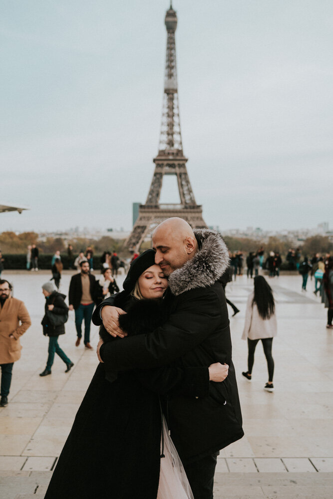 Couple snuggling in front of eiffel tower during paris engagement session
