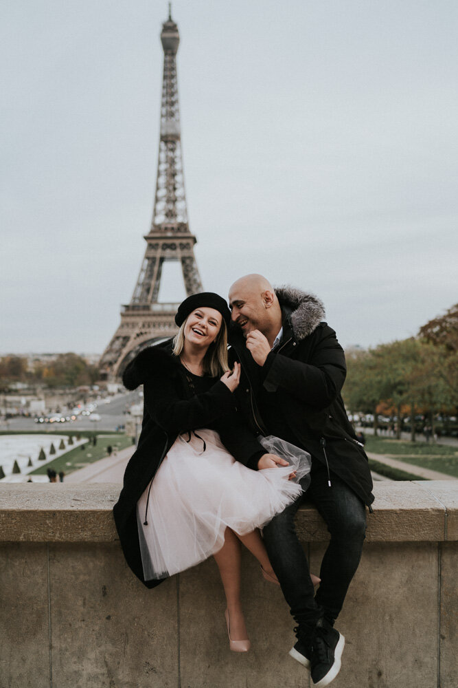 Couple laughing in front of eiffel tower during paris engagement session