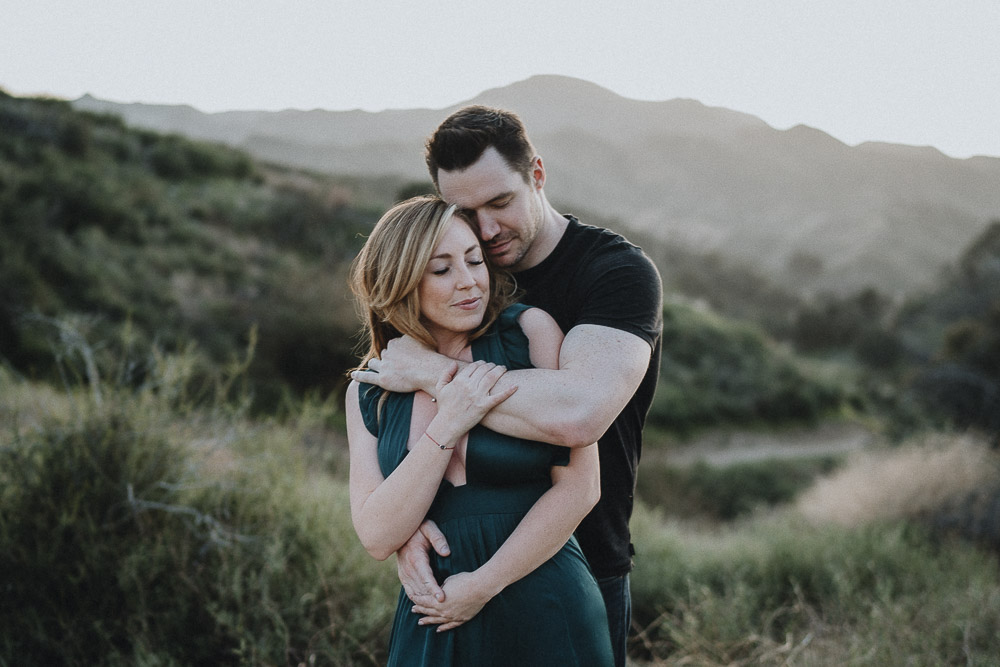 Couple cuddles during engagement session in los angeles canyon