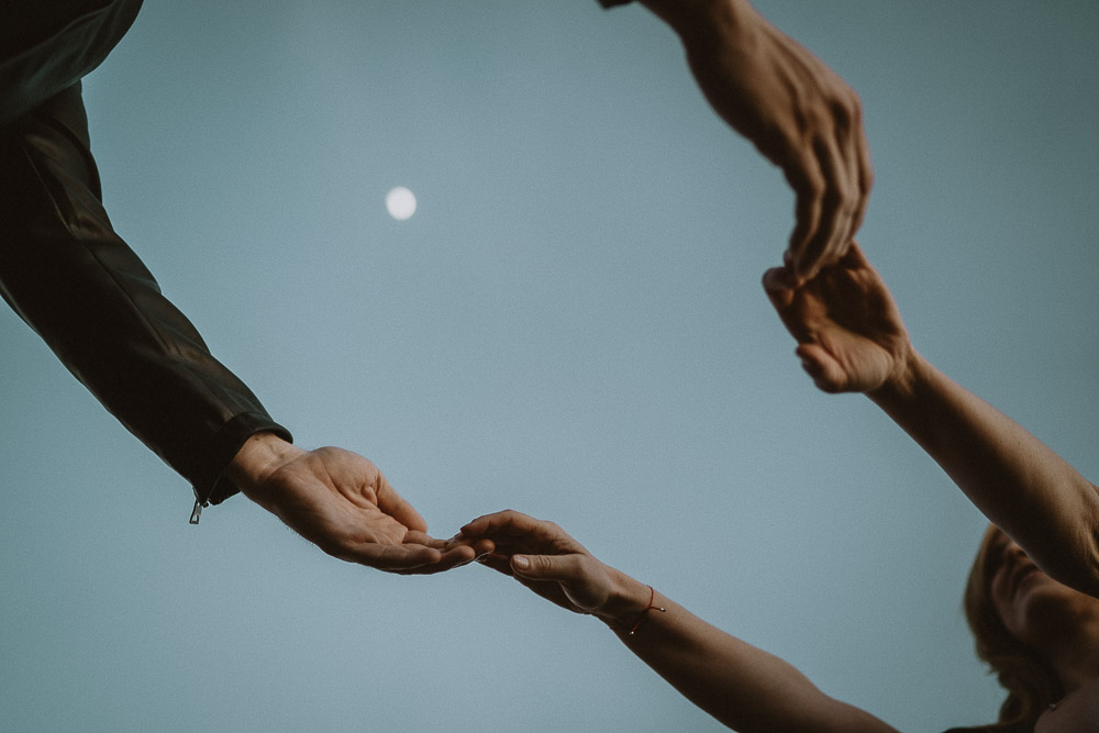 Couple holding hands under the moon at blue hour