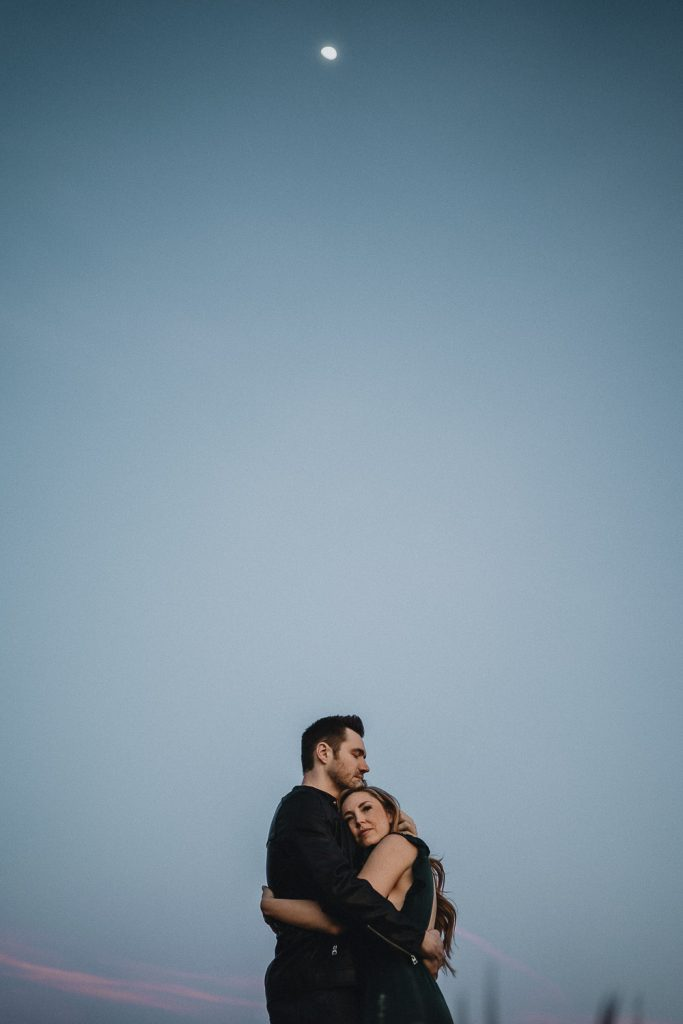 Couple hugging at blue hour with moon up in the sky