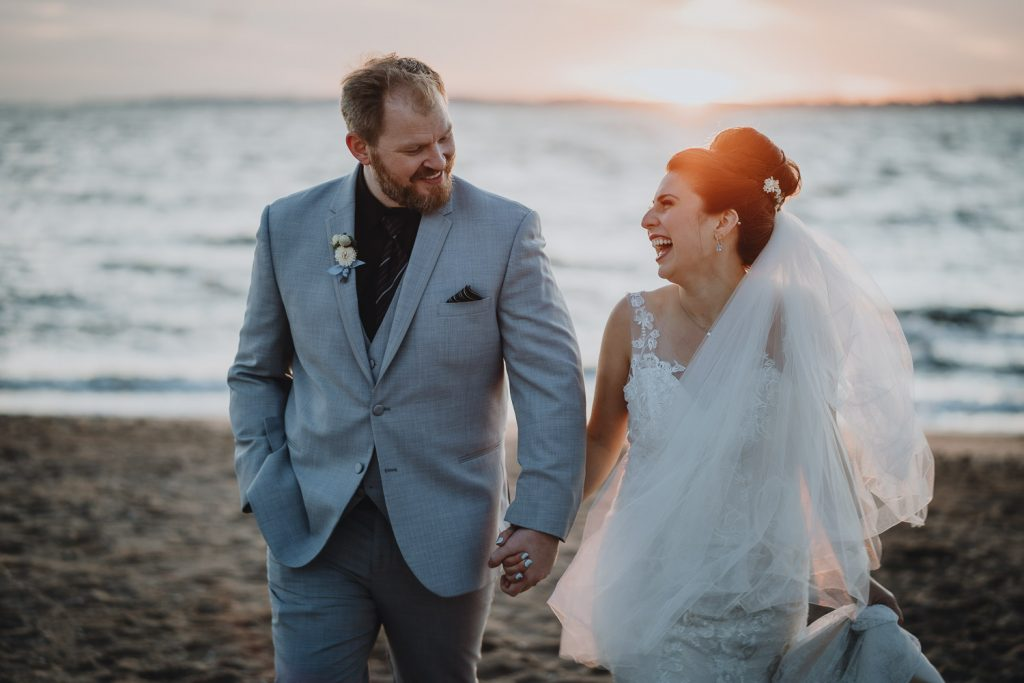 Groom and bride hold hands and laugh at beach wedding in long island