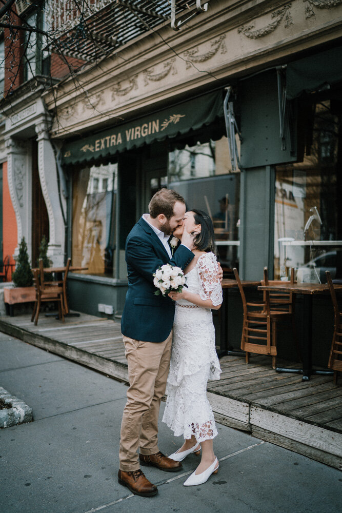 Bride and groom kiss in front of nyc restaurant during elopement