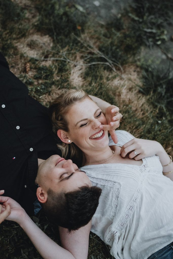 Couple lying down in grass during west point engagement session