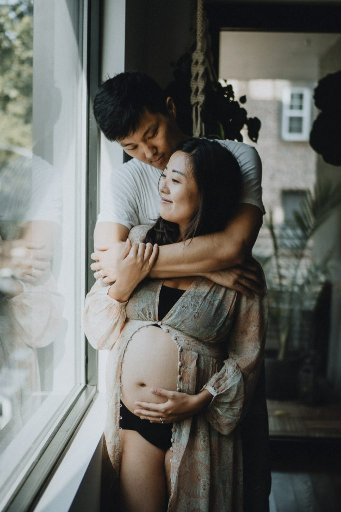 Expecting couple snuggling at home during maternity session in brooklyn