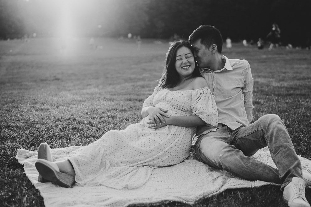 Expecting couple laughs in prospect park during maternity session