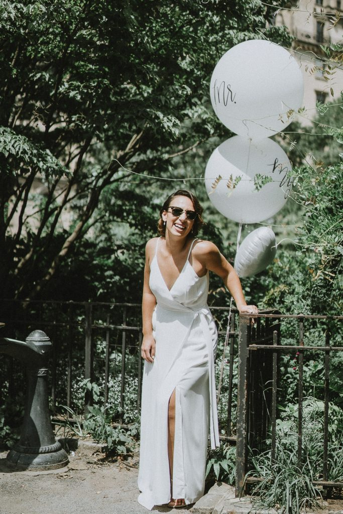 Free-spirited bride laughing in nyc park on wedding day