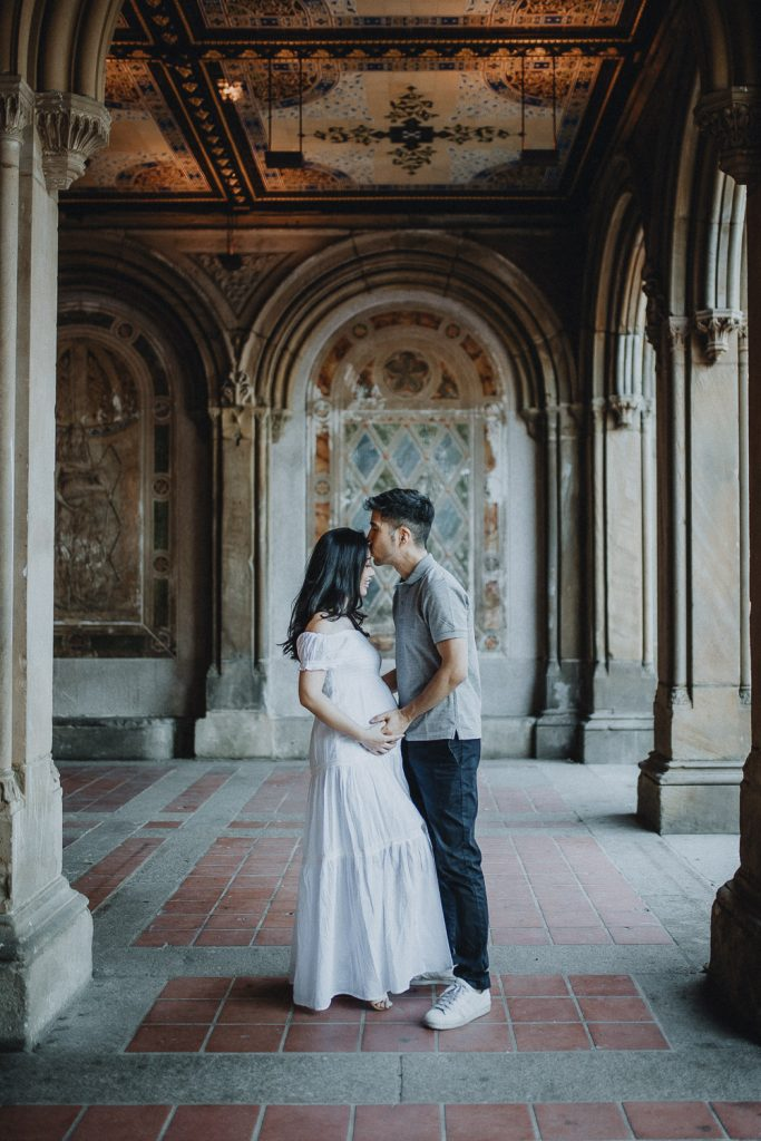 Expecting couple in central park at bethesda terrace during maternity photoshoot