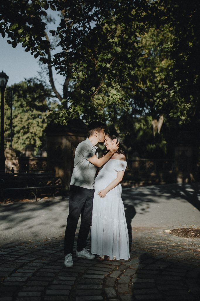 Expecting couple snuggling in central park during maternity photoshoot