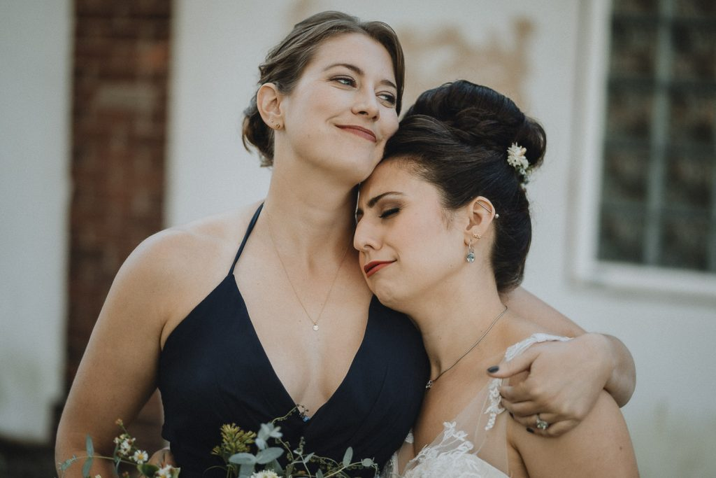 Bride snuggles with maid of honor before hudson valley wedding