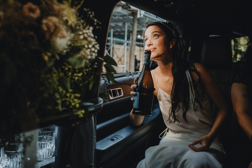 Bride drinks champagne in limo at nyc fall wedding