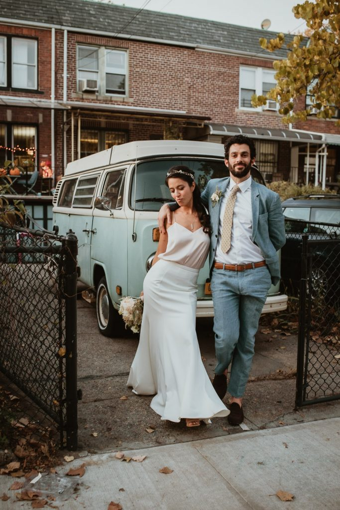 Bride and groom by old minivan at fall brooklyn wedding