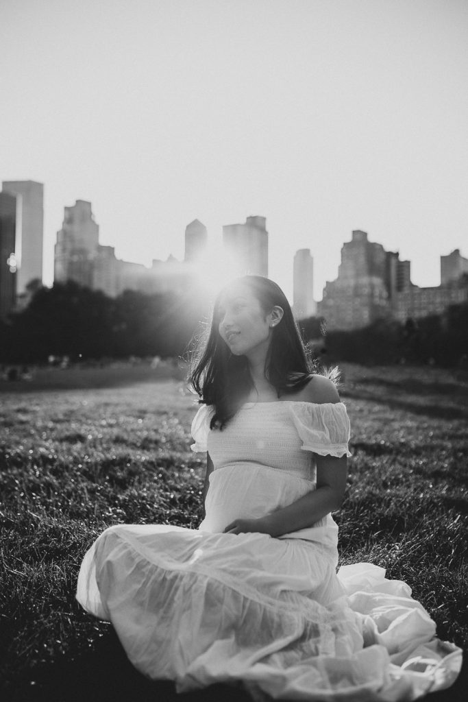 Pregnant woman in central park at golden hour during maternity photoshoot