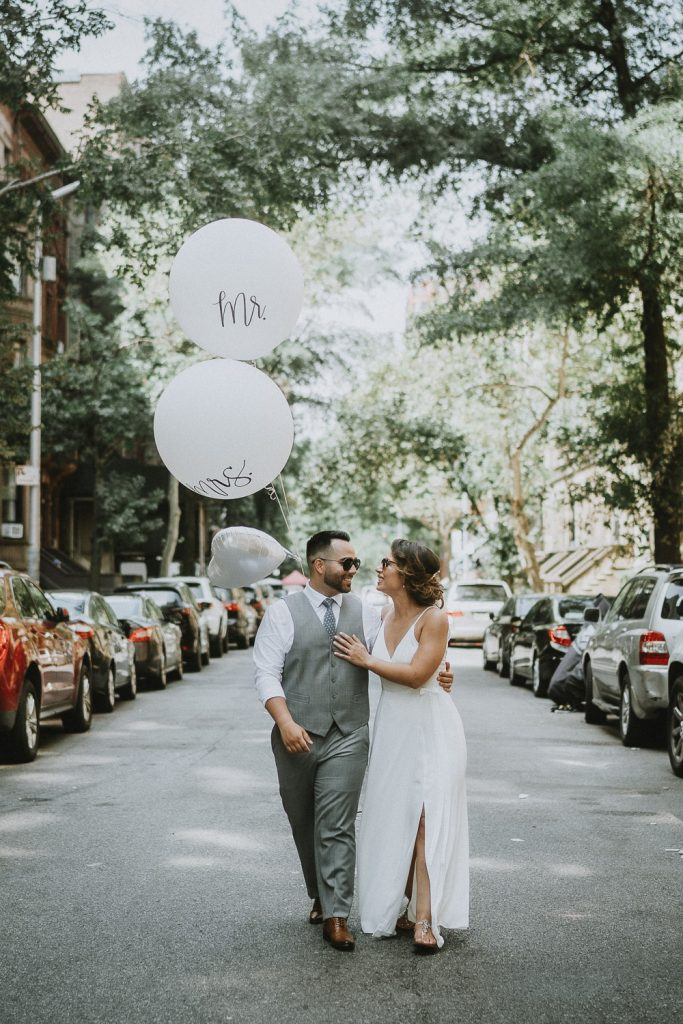 Bride and groom in nyc street with balloons on wedding day