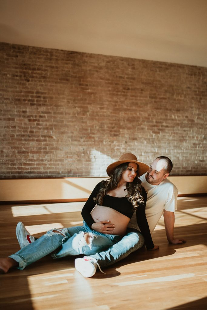 Expecting couple during intimate maternity session in nyc home