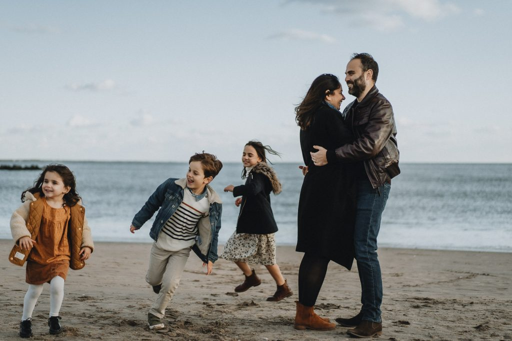 Parents play with three kids during family session at coney island beach