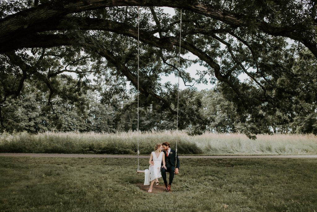 Bride and groom on swing at red maple vineyard